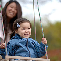 girl on swing with mother behind
